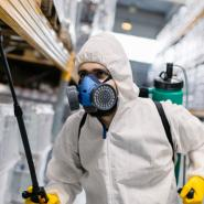man in protective suit spraying the inside of a warehouse for pests